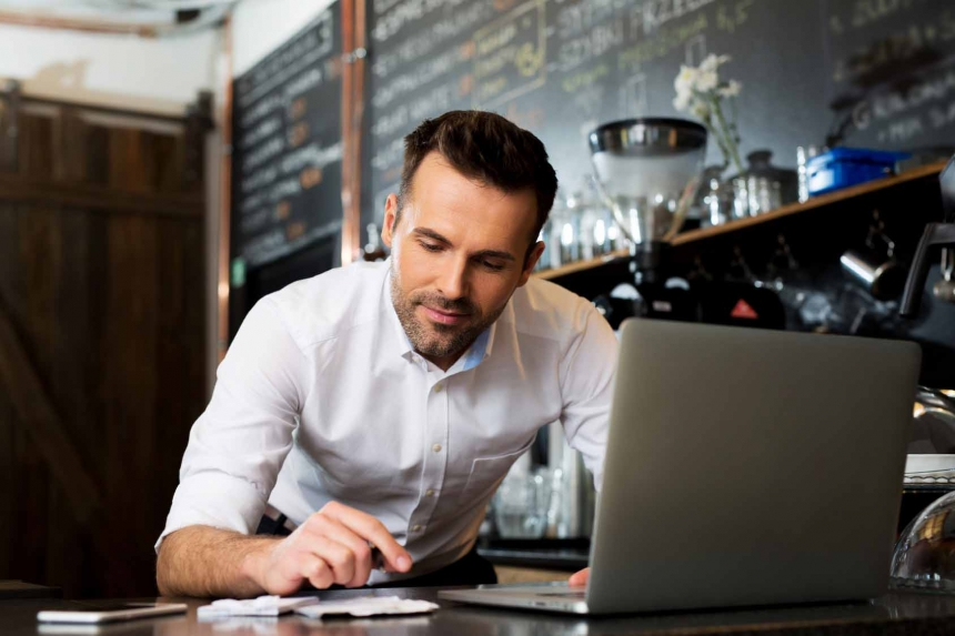 Cafe manager counting recipes with laptop
