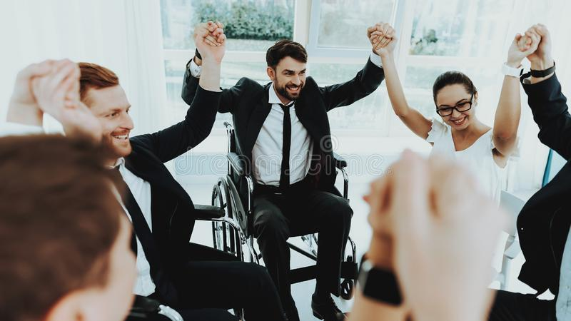 Group Disabled People Raise Hands in Bright Office royalty free stock photography