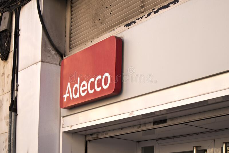 Logo on the facade of an office of the temporary employment agency Adecco stock photo