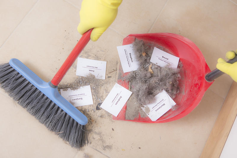 Staff reduction concept - Cutting staff and employee Job Reduction. Dismissal. Office cleaner throw in the debris staff business cards. Crisis management and royalty free stock images