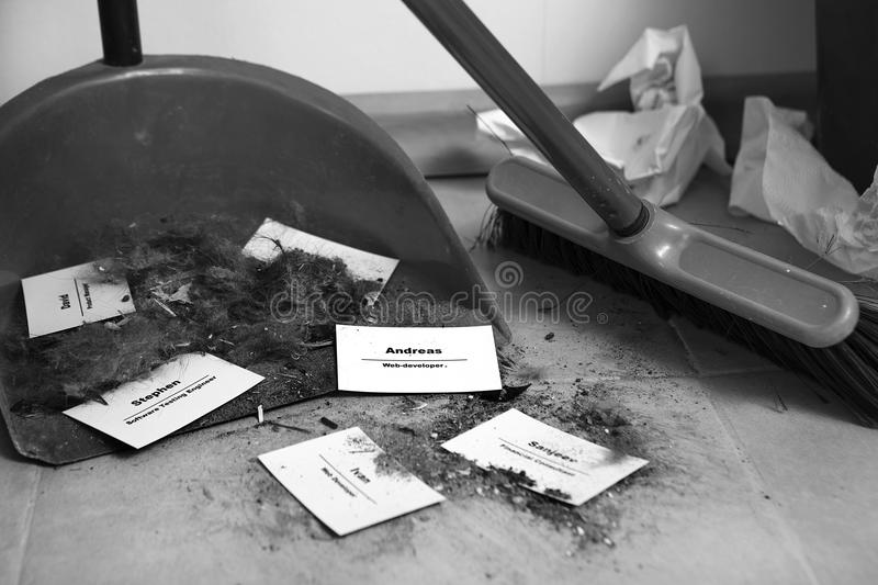 Staff reduction concept - Cutting staff and employee Job Reduction. Dismissal. Office cleaner throw in the debris staff business cards. Crisis management and stock photo