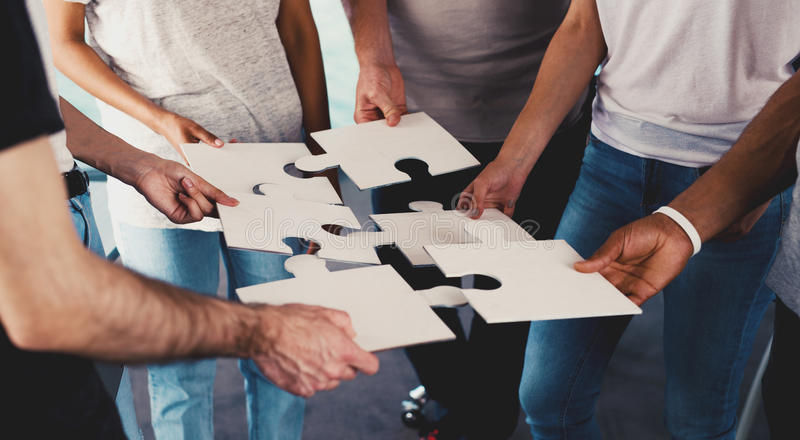 Team of businessmen work together for one goal. Concept of unity and partnership. Team of businessmen work together for one goal with puzzles. Concept of unity royalty free stock images