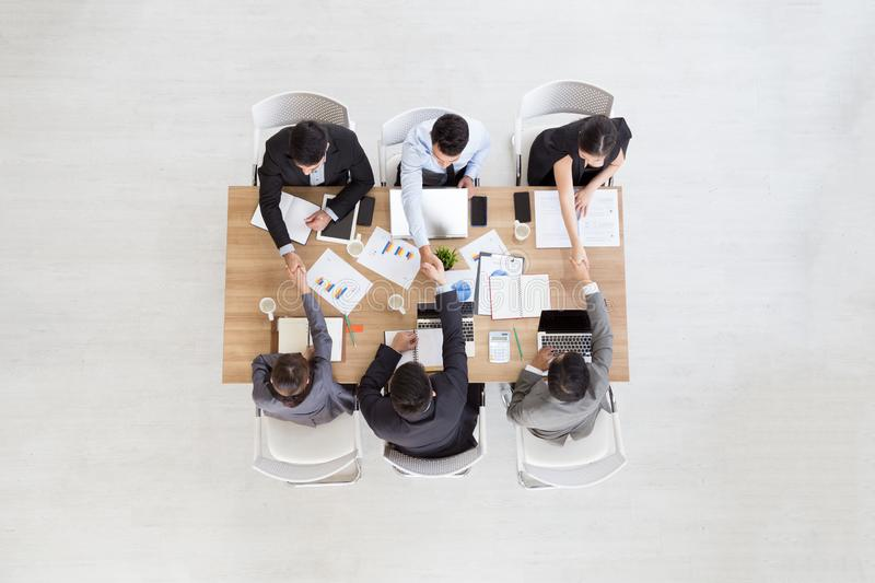 Top view of businessmen shaking hands sitting at conference table during team meeting, stock photos