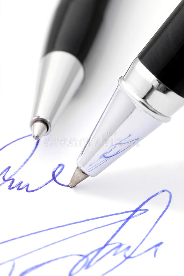 Writing a handwritten signature. Close-up of pen writing the signature stock photography
